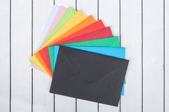 Multi colored envelopes on white wooden background Stock Images