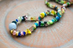 Multi-colored ethnic beads on a brown clay plate. Beads of different bright natural semiprecious stones.Close up Selective focus stock photo