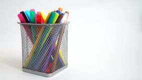 Multi-colored felt-tip pens stand in a mesh transparent glass stock photo