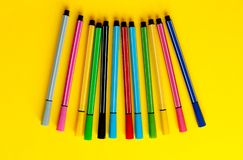 Multi-colored felt-tip pens on yellow background. Top view,business, office supplies. School office supplies. Minimal style. Colo. Rful marker pen set. Vivid stock photos