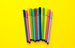Multi-colored felt-tip pens on yellow background. Top view,business, office supplies. School office supplies. Minimal style. Colo. Rful marker pen set. Vivid stock image