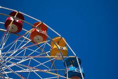 Multi-colored ferris wheel against a blue sky Stock Photography
