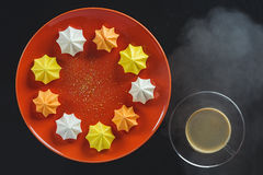 Multi-colored figured cookies on a round orange plate and a cup of hot coffee on a black background. Multi-colored figured cookies on a round ceramic orange stock image