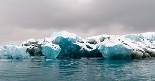 Multi-colored floating glacial ice with snow cover. Antarctic Peninsula royalty free stock image