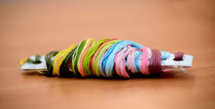 Multi-colored floss on the table. Multicolored floss in rolled on the table Royalty Free Stock Photos