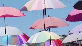 Multi-colored flying umbrellas. Umbrellas are hung high for a string. They can be heard from the wind in the sky stock video footage
