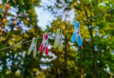 Multi-colored four clothes pegs attached to a long rope in the courtyard royalty free stock photography