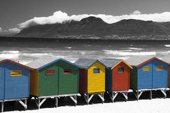 Multi colored fun in the sun. Beach huts with Black and White  mountain backdrop and ocean with strong contrast Royalty Free Stock Image