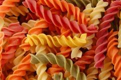 Multi colored fusilli twirls pasta. Many different flavors of fusilli twirls pasta. Italian food background detail Royalty Free Stock Photography