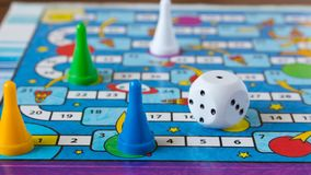 Multi-colored game chips with dice on the playing board. Board game.  stock images
