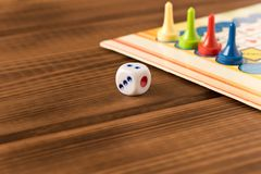 Multi-colored game chips with dice on the playing board. Board game concept stock photography