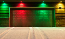 Multi-Colored Garage Door and Snowy Driveway. Red, green and yellow lights decorate the front of a garage Stock Photos