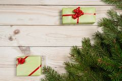 Multi-colored gift boxes and spruce branches on a wooden background. Christmas background, top view. Flat lay. Christmas gift box. Holiday greeting card. Copy stock photos