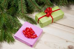 Multi-colored gift boxes and spruce branches on a wooden background. Christmas background, top view. Flat lay. Christmas gift box. Holiday greeting card. Copy stock image
