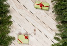 Multi-colored gift boxes and spruce branches on a wooden background. Christmas background, top view. Flat lay. Christmas gift box. Holiday greeting card. Copy royalty free stock photo