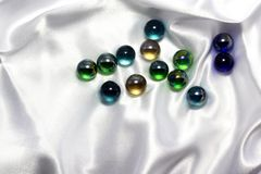 Multi-colored glass balls. Abstract background with multi-colored glass beads on a white satin Stock Photos