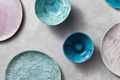 Multi-colored glay vintage handmade dishes. Flat lay. Set of porcelain blue bowls on a gray concrete table. Decorative pottery - bowls, plates covered with Stock Images