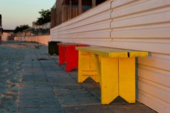 Colorful benches against the backdrop of stone gray tiles and sand, beach Royalty Free Stock Photo