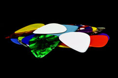Multi-colored guitar pick. On a black background Royalty Free Stock Photography