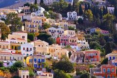 Multi-colored huizen op de kust van de oude haven op het Eiland Symi Kust van Egeïsch Griekenland stock foto