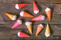 Multi-colored ice cream cones on old boards. Sweet delicacies in the form of horns from wafers with cream on a table from old gray boards Stock Photo