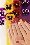 Multi-colored juicy manicure on short female nails royalty free stock photo