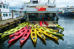 Multi-colored kayaks on adventure cruise ship. Seattle, WA, USA April 30, 2017: Crew members of cruise boat Wilderness Discoverer check and clean kayaks before Stock Photo