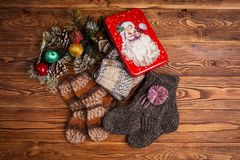 Multi-colored knitted baby socks, Christmas decorations and a metal box with the image of Santa Claus on a wooden background royalty free stock photography