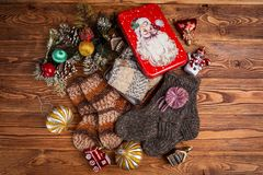 Multi-colored knitted baby socks, Christmas decorations and a metal box with the image of Santa Claus on a wooden background stock photos
