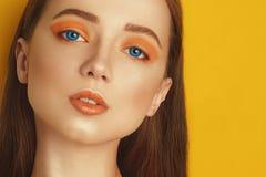 Multi-colored lenses for eyes. Blue lenses, green lenses. Beauty Model Girl with orange professional makeup. Orange eye shadow royalty free stock photos