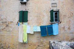 Multi-colored linen is dried outside the window of an old house. In Montenegro Royalty Free Stock Photos