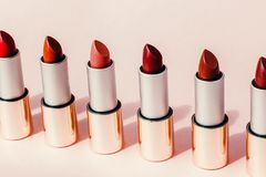 Multi-colored lipsticks stand in a row on a pink background. The concept of different, collections and beauty. Red, pink and
