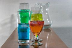 Group of glasses with colorful water on wood table. Multi colored liquid in pretty glasses with iceon table royalty free stock images