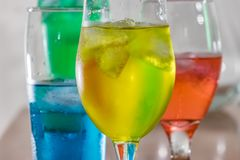 Various glasses full of water. Multi colored liquid in pretty glasses with iceon table royalty free stock image