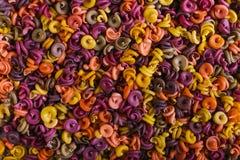 Multi-colored macaroni van een ongebruikelijke vorm met natuurlijke plantaardige kleurstoffen achtergrondclose-up royalty-vrije stock afbeeldingen