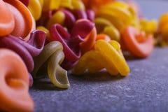 Multi-colored macaroni van een ongebruikelijke vorm met natuurlijke plantaardige kleurstoffen Macro dichte omhooggaand als achter stock foto's