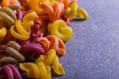 Multi-colored macaroni van een ongebruikelijke vorm met natuurlijke plantaardige kleurstoffen Macro dichte omhooggaand als achter stock afbeelding