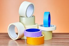 Multi colored multipurpose adhesive tape rolls lie on table. royalty free stock image
