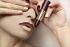 Multi-colored nail design.Trendy Burgundy nail Polish and lip makeup. royalty free stock images