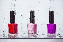 Multi-colored nail polish bottles in water spray, manicure stock photography