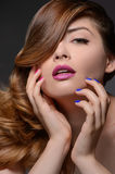 Multi colored nails. Portrait of beautiful women touching face w Stock Images