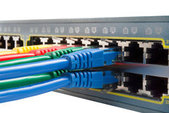 Multi Colored Network Cables Connected to Switch. Bunch of Colored ethernet network cables connected to a switch isolated on white background. Top view Stock Photo