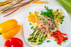 Multi-colored noodles with sesame, vegetables and herbs stock image