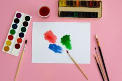 Multi-colored objects for drawing and creativity for children lie on a pink background. Bright watercolor paints, pencils, brushes stock photography