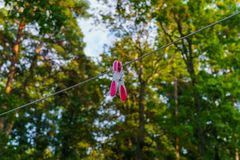 Multi-colored one clothes peg attached to a long rope, in the courtyard royalty free stock image