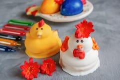 Multi-colored paaseieren liggen naast verf voor het kleuren en marsepein de cakes van Pasen in de vorm van kippen royalty-vrije stock foto's