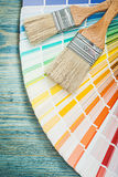 Multi colored pantone fan paint brushes on wooden board construc Royalty Free Stock Photo