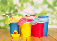 Multi-colored paper cups, straws on  green abstract background. Royalty Free Stock Photography