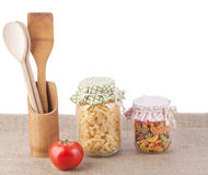 ЭMulti-colored pasta in a glass jar. Multicolored pasta in glass jars tied rag covers royalty free stock photo