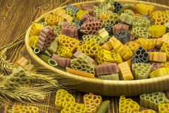 Multi-colored pasta in a wooden bowl on the table. Colored pasta close-ap  as background royalty free stock photography